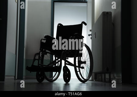Silhouette Of Empty Wheelchair Parked In Hospital Corridor - Stock Photo