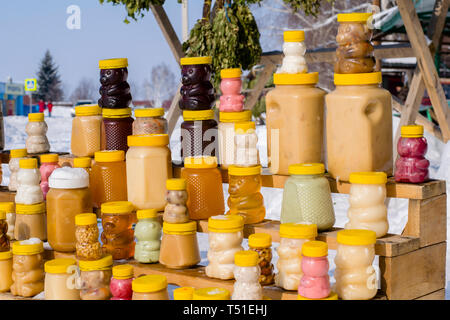 sale of honey and bath brooms on the counter on the street in winter - Stock Photo