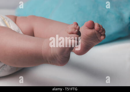 Cute plump legs of a newborn baby on a background of white and blue plaid - Stock Photo