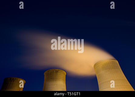 Three isolated cooling towers at night.