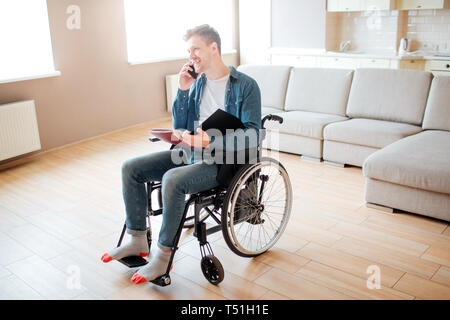 Young man in wheelchair. Person with special needs. Disability. Student sitting and talking on phone. Holding opened book in hands - Stock Photo