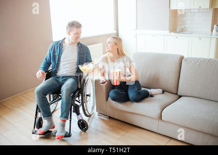 Young man with disability sitting beside woman on sofa. They look at each other and sile. Watching movie. Home cinema. Love - Stock Photo