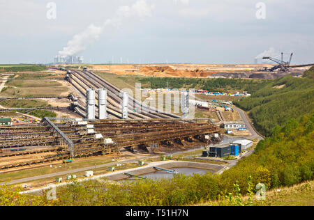 A lignite surface mine with conveyor belts leading to a distant coal power station. - Stock Photo