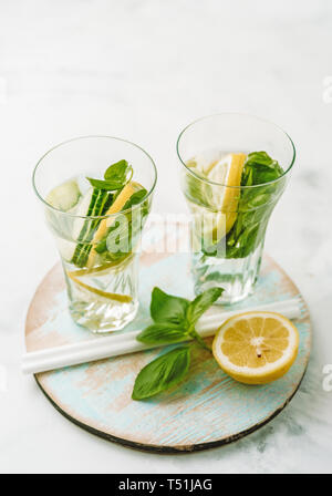 Infused water in two glasses with lemon, cucmber and basil - Stock Photo