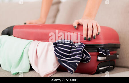 Packing valise. Woman trying to close full suitcase - Stock Photo