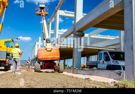 Rigger is in high elevated cherry picker, he is moving over construction site. - Stock Photo