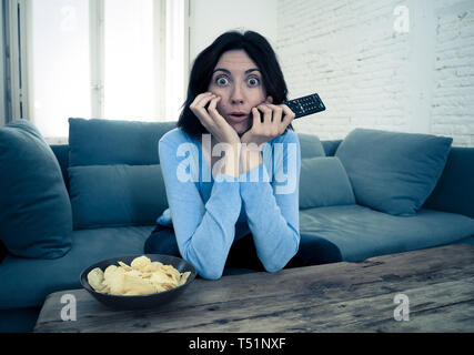 Lifestyle portrait of young woman feeling scared and shocked holding her head in amazement while watching television grabbing remote control. In horro - Stock Photo