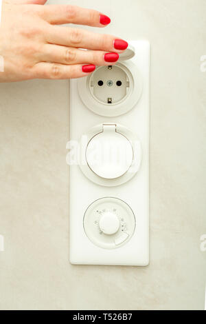 Female hand lifts the protective cover on the electrical outlet. - Stock Photo