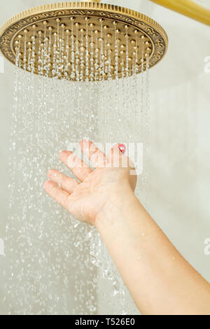 Famale hand check water temperature in the shower . - Stock Photo