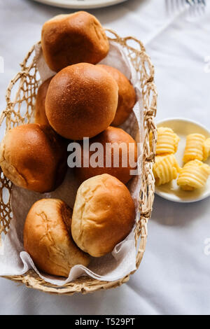 Close up of freshly baked bread rolls in basket and butter in small plate on dinning table - Stock Photo