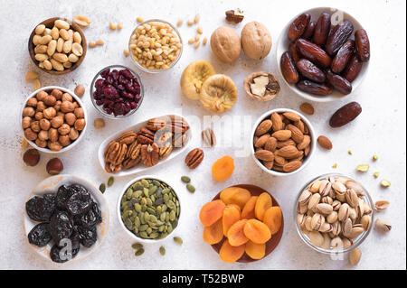 Dried fruits and Nuts in bowls on white background, top view. Healthy snack - assortment of organic dry fruits and various nuts. - Stock Photo