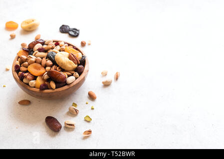 Mixed nuts and dried fruits in wooden bowl on white background, copy space. Healthy snack - mix of organic nuts and dry fruits. - Stock Photo