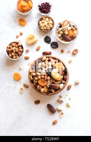 Mixed nuts and dried fruits in wooden bowl on white background, top view. Healthy snack - mix of organic nuts and dry fruits. - Stock Photo