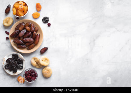 Dried fruits in bowls on white marble background, top view, copy space. Healthy snack - assortment of organic dry fruits. - Stock Photo