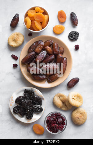 Dried fruits in bowls on white marble background, top view. Healthy snack - assortment of organic dry fruits. - Stock Photo