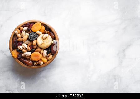 Mixed nuts and dried fruits in wooden bowl on white marble background, copy space. Healthy snack - mix of organic nuts and dry fruits. - Stock Photo