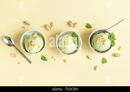 Pistachio Ice Cream on yellow background, top view. Green pistachio gelato in bowls with pistachio nuts and mint. - Stock Photo