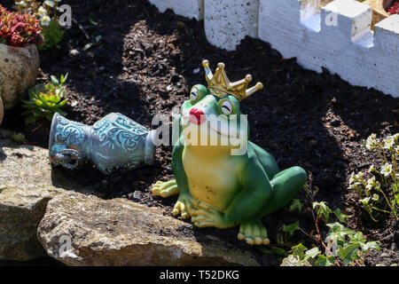 Decorative princess frog in the garden by the pond. - Stock Photo
