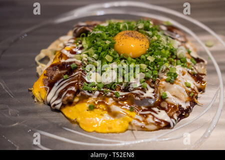 Okonomiyaki, a Japanese pizza / pancake containing a variety of ingredients, on the pan - Stock Photo