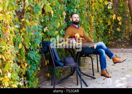 Beard man is sitting in a cafe on the background of autumn leaves. Brunette in yellow sweater drinks and get warm mulled wine in a cafe or garden. - Stock Photo