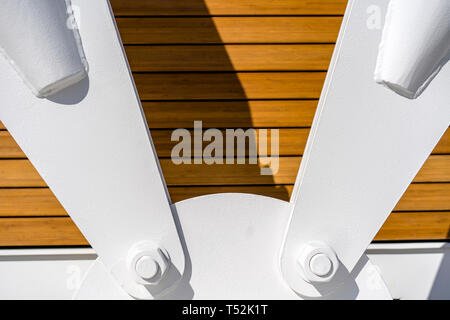 Powerful metal fastening of the bridge pull lines from flanges, fixed on an anchor base with large diameter threaded bolts and painted white against t - Stock Photo