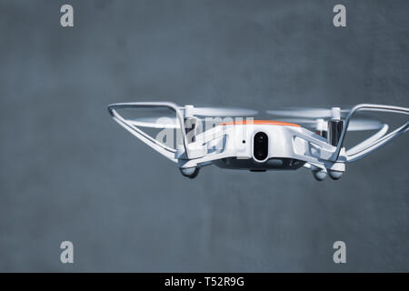 Quadcopter drone in flight with digital camera. New technologies in photo and video filming. - Stock Photo