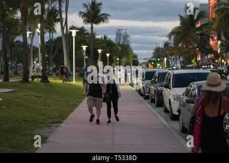 Man Women Couple Walking along Ocean Drive enjoying an evening stroll - Stock Photo