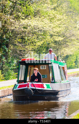 Front view of a narrow boat moving along the Shropshire Union Canal, UK. Canal boat and people back lit on a sunny spring day. - Stock Photo