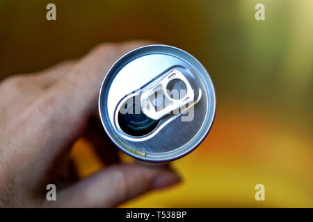 A man holds an open aluminum can of drink. View from above. Shallow depth of field. Central composition. - Stock Photo