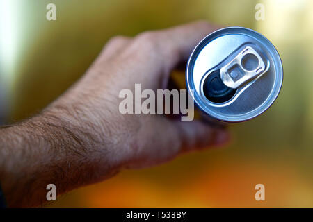 Male hand holding an open aluminum can of drink. View from above. Shallow depth of field. - Stock Photo