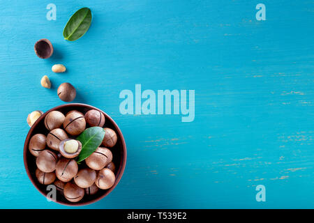 Australian macadamia nuts with leaf in plate and scattering on blue wooden background - Stock Photo