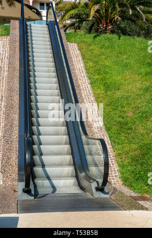 A modern electronic system of many moving on escalator outdoors on a summer day. - Stock Photo