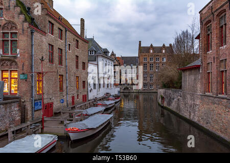 Old street of Bruges with traditional medieval houses of red brick, canal, boat dock and boats on the water. Cityscape of Bruges streets. - Stock Photo
