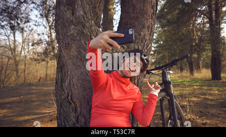 Young caucasian woman athlete tourist cyclist uses hand smart phone photo of herself selfie sitting near tree in coniferous forest outside the city - Stock Photo
