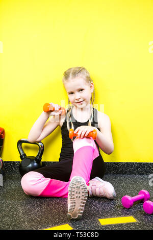 Theme sports and health children. Little funny child Caucasian girl with pigtails, sits resting break on floor in gym. Athlete dumbbell equipments for - Stock Photo