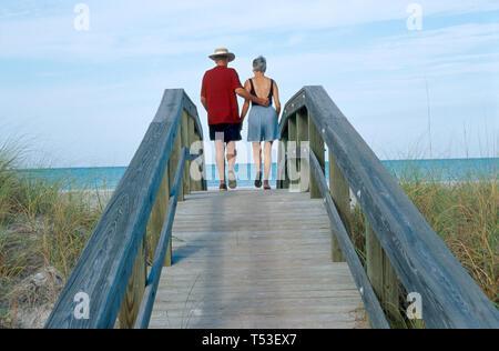Florida Gulf Coast Charlotte County Don Pedro & Knight Islands Palm Resort couple boardwalk natural dunes - Stock Photo