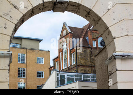 Brick multi-level house with large beautiful windows. Picture taken through the old arch. Central London. - Stock Photo