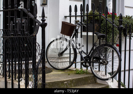 Vintage bicycle with basket on the porch. Entrance Door to residential building in London. Typical door in the English style - Stock Photo