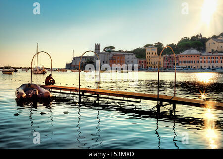 Landscape of backlit by bright sunset of beaches jetty in silence bay at small town Sestri Levante. Genova Province, Liguria, Italy - Stock Photo