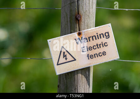 A crooked sign warning people that an electric fence is present. The sign is attached to a wire fence with a green background. - Stock Photo