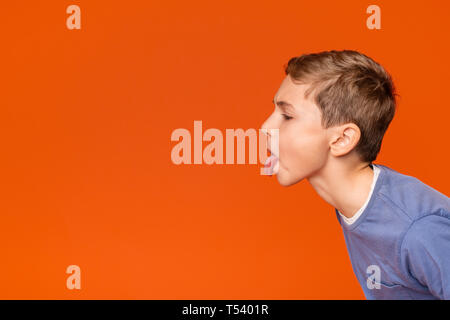 Little boy teasing someone, showing tongue and making face at free space aside, orange background - Stock Photo