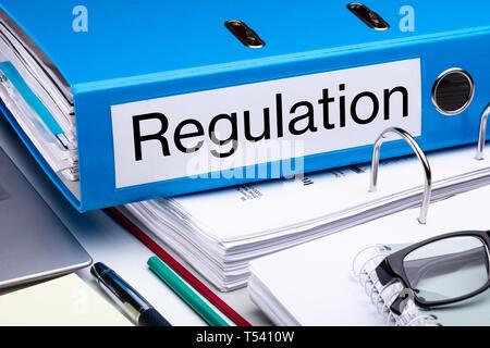 Blue Regulation Folder And Files On Business Desk - Stock Photo