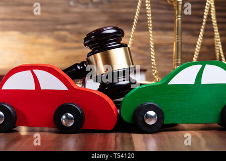 Close-up Of Two Green And Red Wooden Cars On Desk In Courtroom - Stock Photo