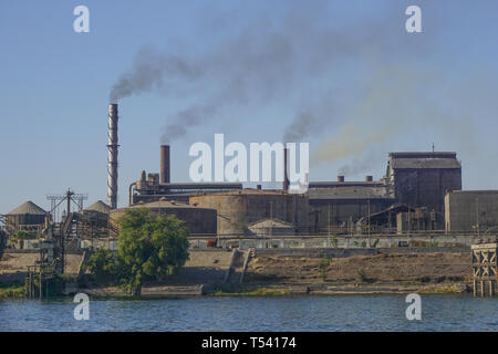 Nile River, Egypt: A factory on the east bank of the Nile River emits smoke from several chimneys. - Stock Photo
