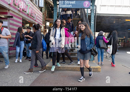 Teenage students returning from school and others emerge from the 7 train on 82nd Street in Jackson Heights, Queens, New York City - Stock Photo