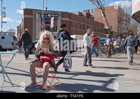 A street scene featuring a seated woman with long blond hair texting on her cell phone. In Jackson Heights, Queens, New York City. - Stock Photo