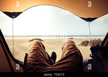 Alternative vacation concept with man in trekking clothes laying outside the tent campiing free at the beach looking the ocean horizon and enjoying th - Stock Photo
