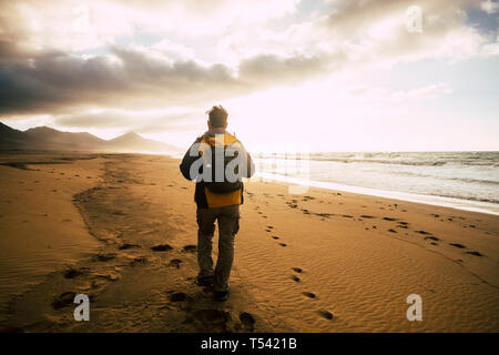People in back view walking alone with his backpack on the desolation beautiful wild beach for alternative concept of tourism vacation - adventure and - Stock Photo