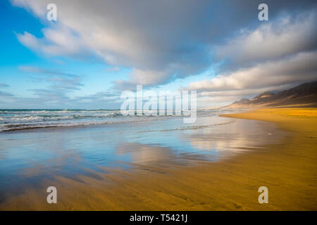 Lonely beach coloured and reflected with beautiful mountain background  with cloudy sky - summer tropical vacation concept in free sandy scenic place  - Stock Photo