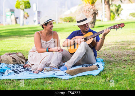 Romantic happy nice caucasian couple people playing a guitar for romantic activity sitting on a meadow in outdoor nature park together - love and rela - Stock Photo